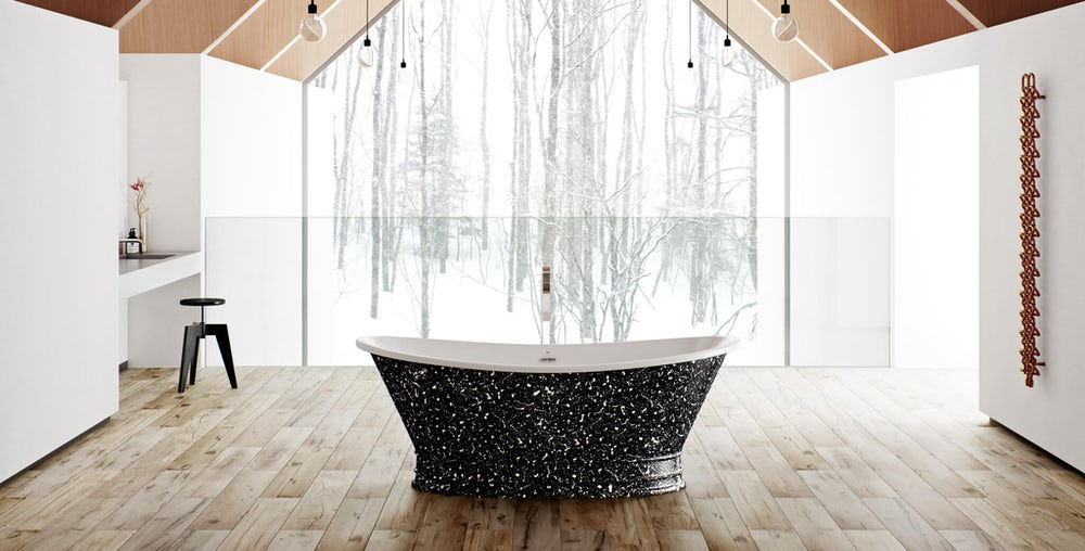 Black and white speckled Balthus freestanding bath in a room with wooden flooring and low hanging lightbulbs